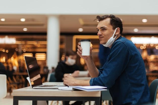 カフェのテーブルに座ってコーヒーのテイクアウトを持つ若い男。コピースペースのある写真
