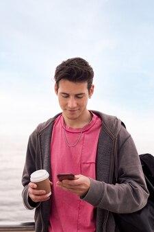 휴대 전화를 사용하여 커피와 함께 젊은 남자