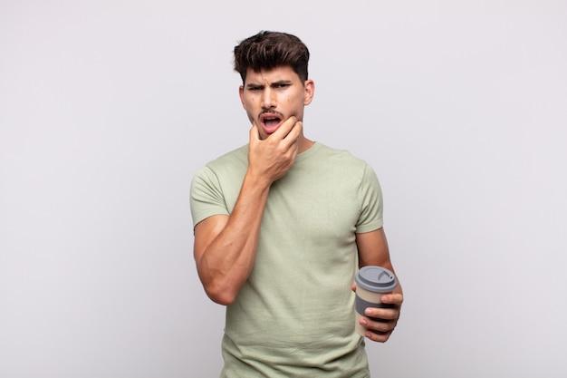 口と目を大きく開いてあごに手を当ててコーヒーを飲んでいる若い男は、不快なショックを感じて、何を言っているのか、すごい