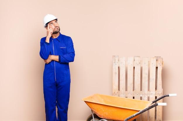 集中した表情で、疑わしい表情で疑問に思って、見上げて、横の建設コンセプトを持つ若い男