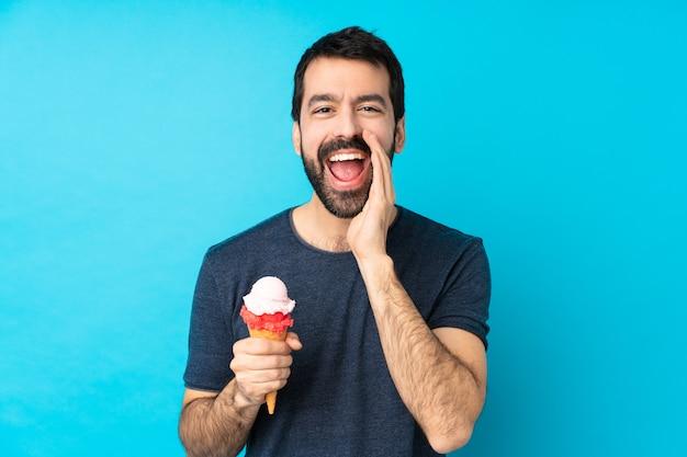 Молодой человек с корнет мороженым над синей стеной кричал с широко открытым ртом