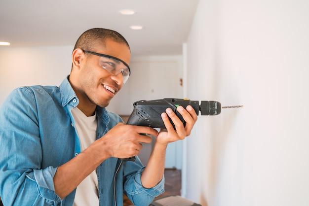 電気ドリルと壁に穴を作る若い男。