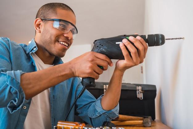 電気ドリルと壁に穴を作る若い男