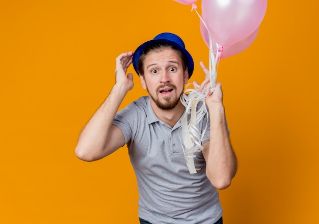 오렌지 벽 위에 서있는 축하 생일 파티를 혼란 찾고 풍선의 무리를 들고 모자와 젊은 남자