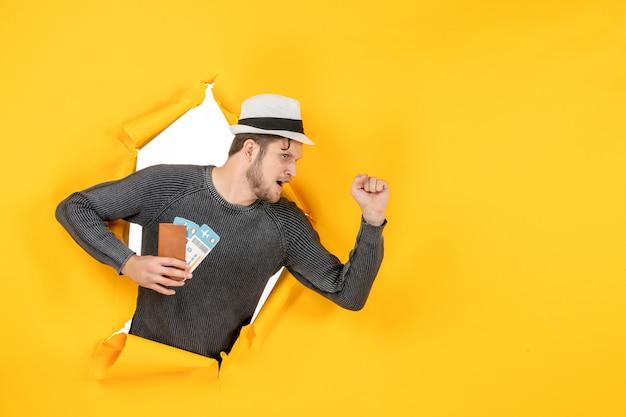 티켓과 함께 외국 여권을 들고 노란색 벽에 찢어진 뭔가에 집중 모자를 가진 젊은 남자