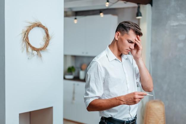 Молодой человек с головной болью, измеряющий температуру домашней жизни