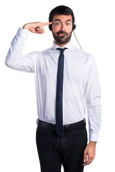 狂ったジェスチャーを作るヘッドセットを持つ若い男