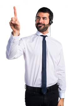 Молодой человек с гарнитурой, касаясь прозрачного экрана