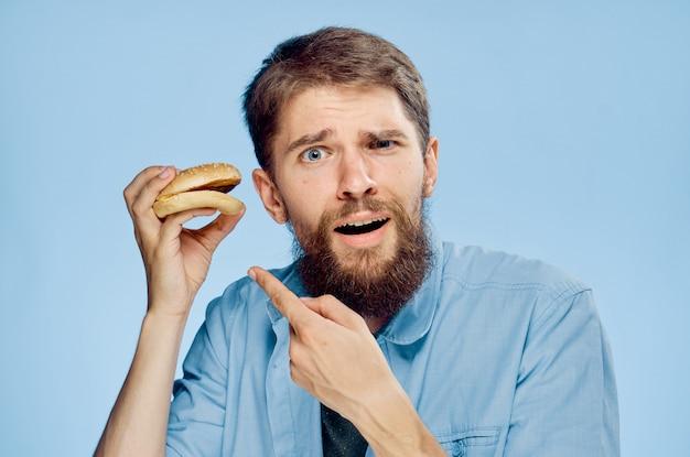 Молодой человек с сочным вкусным гамбургером в руках в студии на заднем плане