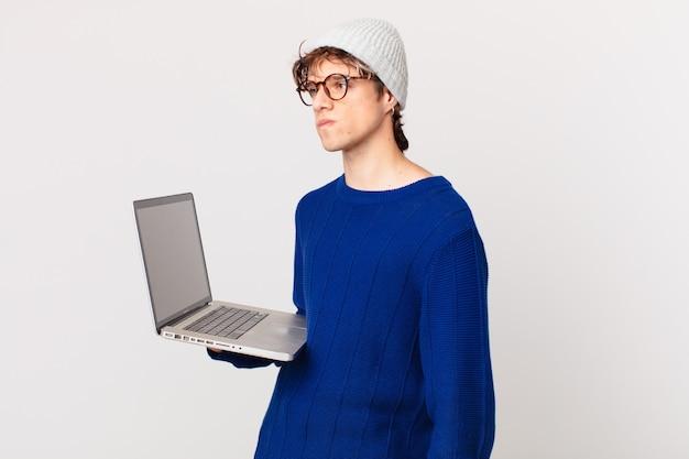 ラップトップを持っている若い男は、悲しみ、動揺、または怒りを感じ、横を向いています