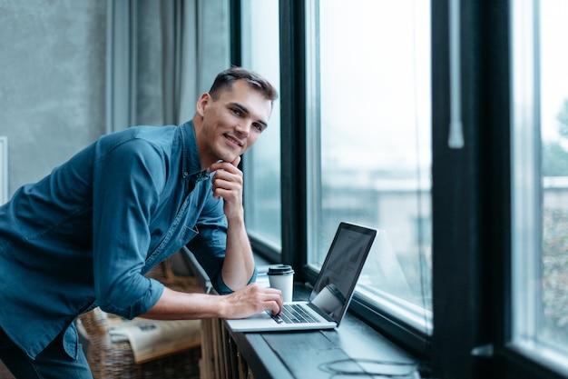 窓の近くに立っているラップトップを持つ若い男