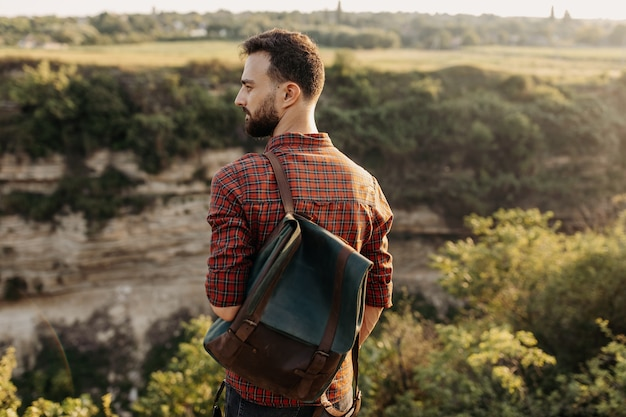 Молодой человек с кожаным рюкзаком на открытом воздухе.