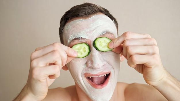顔にマスクをした青年がキュウリの指輪で遊んでしかめっ面をします。
