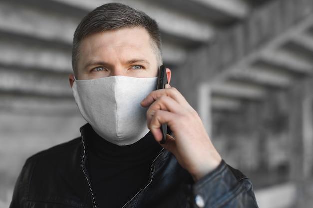 医療用フェイスマスクと通りで手に電話を持つ若者。大気汚染コロナウイルス保護の概念。 covid 19