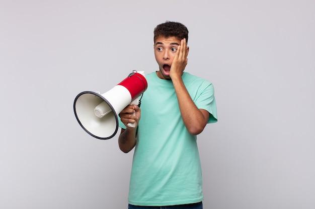 Молодой человек с мегафоном чувствует себя счастливым, взволнованным и удивленным, глядя в сторону обеими руками на лице