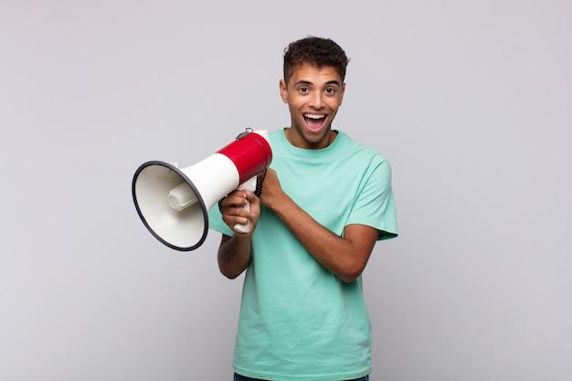 Молодой человек с мегафоном чувствует себя счастливым, позитивным и успешным, мотивированным, когда сталкивается с проблемой или празднует хорошие результаты