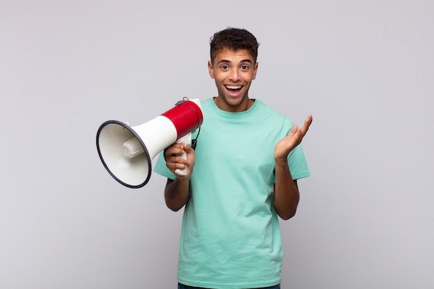 Молодой человек с мегафоном чувствует себя счастливым, удивленным и веселым, улыбается с позитивным настроем, реализует решение или идею