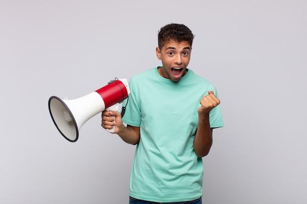Молодой человек с мегафоном чувствует себя потрясенным, взволнованным и счастливым, смеется и празднует успех, говоря: