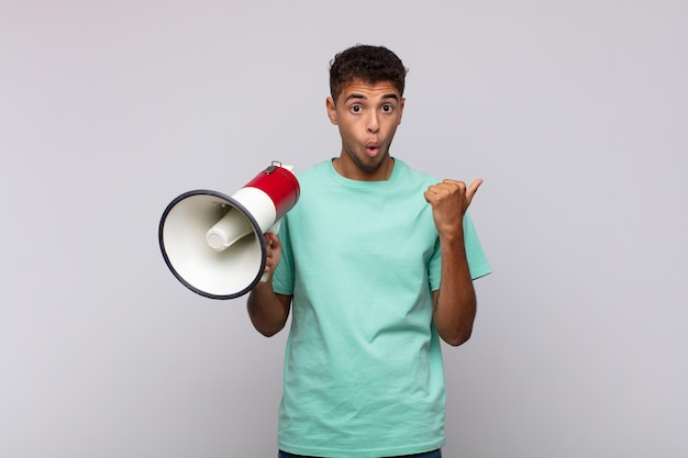 Молодой человек с мегафоном выглядел изумленным и недоверчивым, указывая на объект сбоку и говоря: «вау, невероятно»