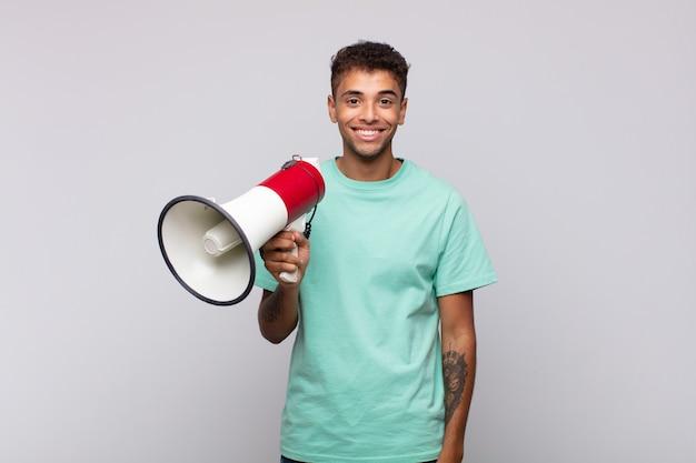 Молодой человек с мегафоном выглядит счастливым и приятно удивленным, взволнованным с очарованным и шокированным выражением лица
