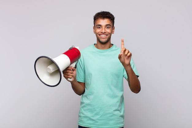 Молодой человек с мегафоном улыбается и выглядит дружелюбно, показывает номер один или первый с рукой вперед, отсчитывая Premium Фотографии