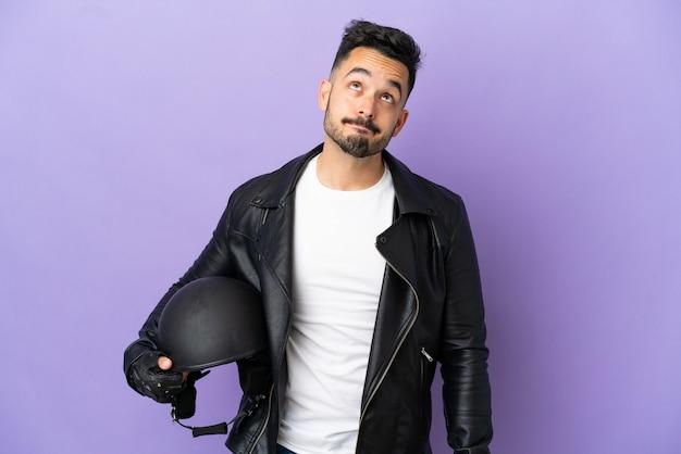 Молодой человек с мотоциклетным шлемом, изолированные на фиолетовом фоне и глядя вверх