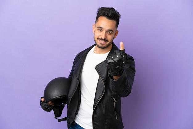 Молодой человек в мотоциклетном шлеме на фиолетовом фоне делает приближающийся жест