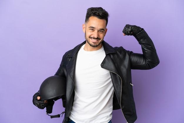 Молодой человек в мотоциклетном шлеме на фиолетовом фоне делает сильный жест