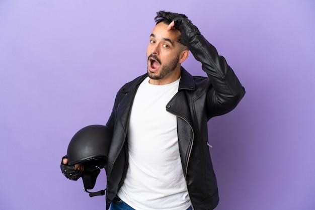 Молодой человек в мотоциклетном шлеме на фиолетовом фоне делает неожиданный жест, глядя в сторону
