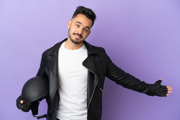 Молодой человек в мотоциклетном шлеме, изолированном на фиолетовом фоне, протягивает руки в сторону, приглашая приехать
