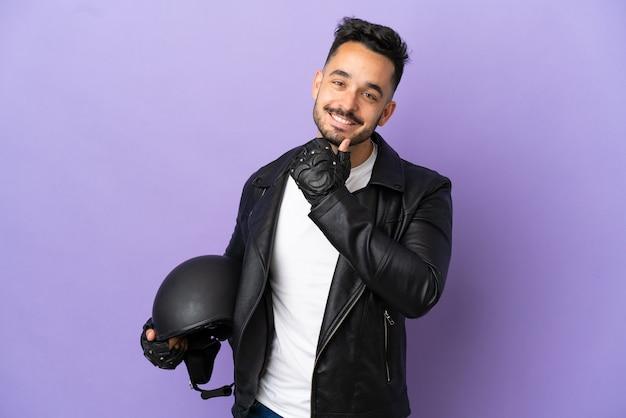 Молодой человек с мотоциклетным шлемом, изолированные на фиолетовом фоне, счастлив и улыбается