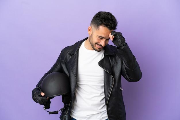 Молодой человек с мотоциклетным шлемом, изолированные на фиолетовом фоне смеясь