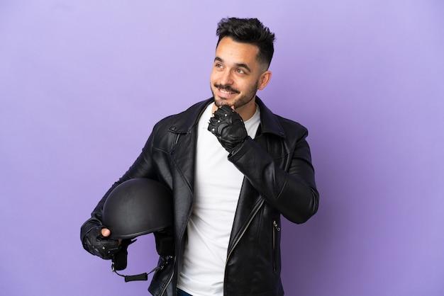 Молодой человек в мотоциклетном шлеме на фиолетовом фоне смотрит в сторону и улыбается