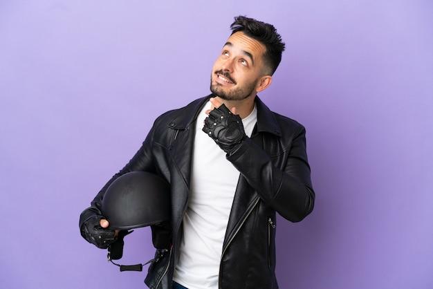 Молодой человек с мотоциклетным шлемом, изолированным на фиолетовом фоне, глядя вверх, улыбаясь
