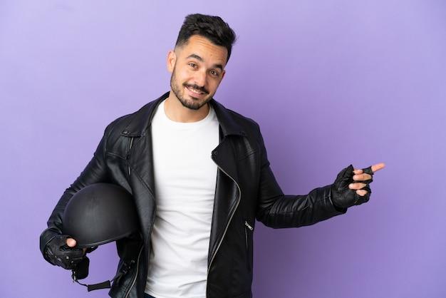 Молодой человек в мотоциклетном шлеме изолирован на фиолетовом фоне, указывая пальцем в сторону
