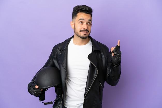 Молодой человек в мотоциклетном шлеме изолирован на фиолетовом фоне, указывая на отличную идею