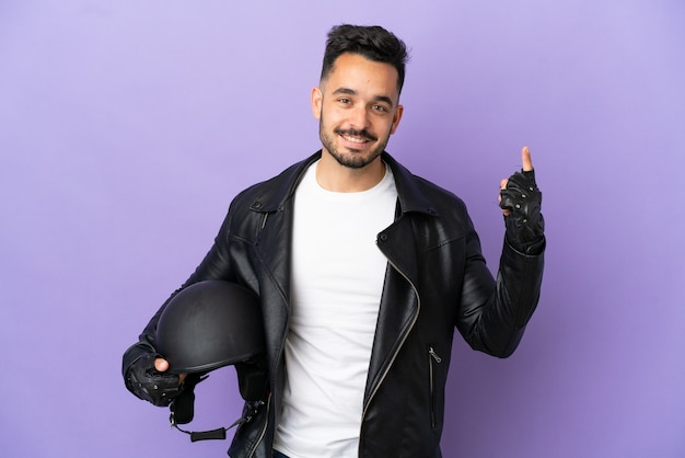 素晴らしいアイデアを指している紫色の背景に分離されたオートバイのヘルメットを持つ若い男