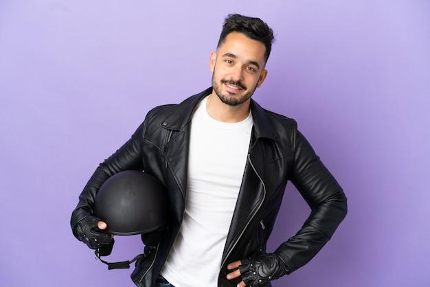 Молодой человек в мотоциклетном шлеме на фиолетовом фоне позирует с руками на бедрах и улыбается