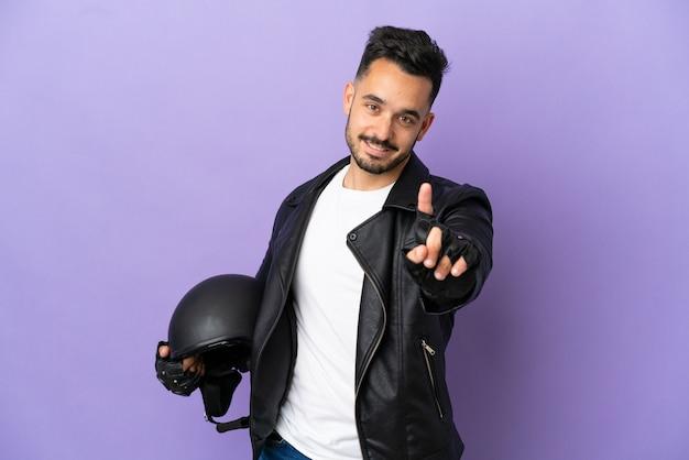 Молодой человек в мотоциклетном шлеме на фиолетовом фоне показывает и поднимает палец