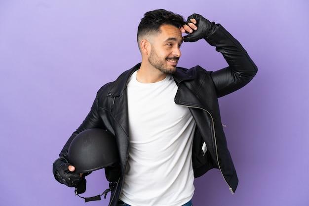 たくさん笑って紫色の背景に分離されたオートバイのヘルメットを持つ若い男