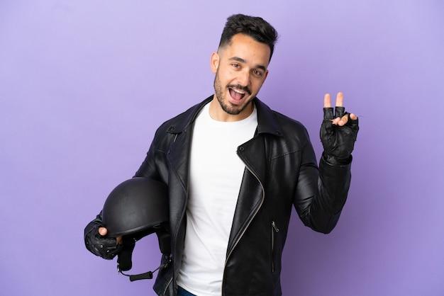 Молодой человек с мотоциклетным шлемом, изолированным на фиолетовом фоне, улыбается и показывает знак победы