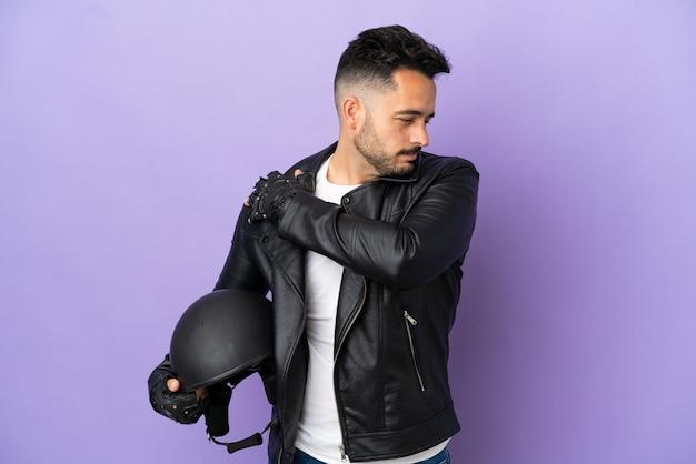 Молодой человек в мотоциклетном шлеме на фиолетовом фоне страдает от боли в плече из-за того, что приложил усилие