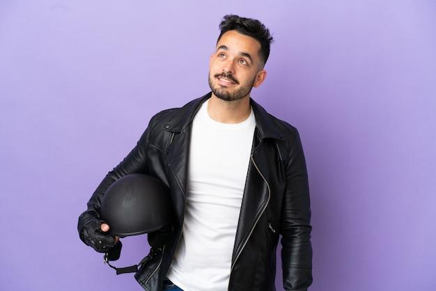 Молодой человек с мотоциклетным шлемом, изолированным на фиолетовом фоне, думает об идее, глядя вверх