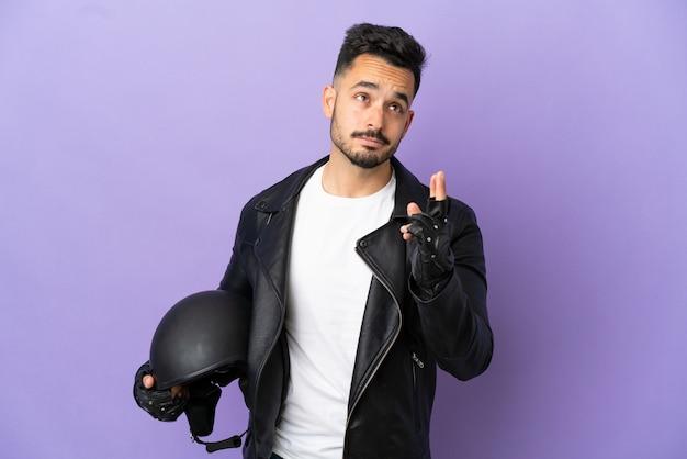 Молодой человек в мотоциклетном шлеме изолирован на фиолетовом фоне со скрещенными пальцами и желает всего наилучшего