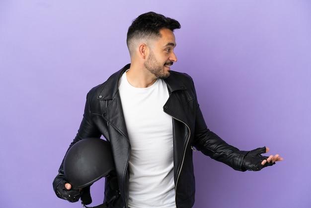 Молодой человек в мотоциклетном шлеме изолирован на фиолетовом фоне с удивленным выражением лица, глядя в сторону
