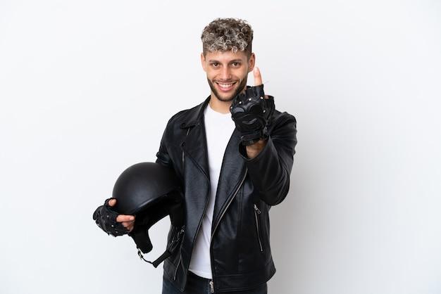 Молодой человек в мотоциклетном шлеме на белом фоне делает приближающийся жест
