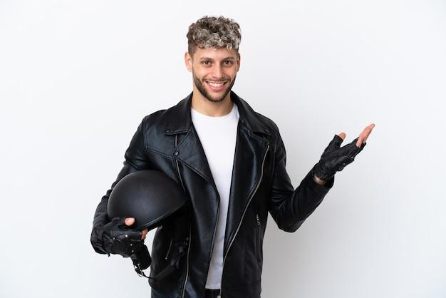 Молодой человек в мотоциклетном шлеме на белом фоне, протягивая руки в сторону, приглашая приехать