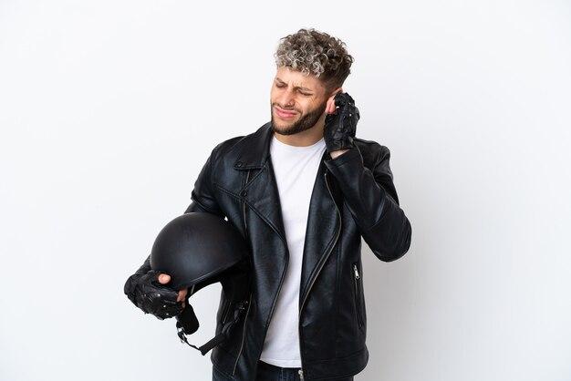 Молодой человек в мотоциклетном шлеме на белом фоне разочарован и закрывает уши