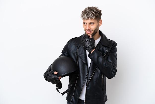 Молодой человек в мотоциклетном шлеме на белом фоне смотрит в сторону и улыбается