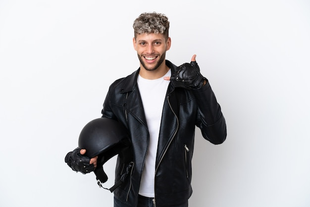 Молодой человек с мотоциклетным шлемом, изолированные на белом фоне, делая телефонный жест. перезвони мне знак